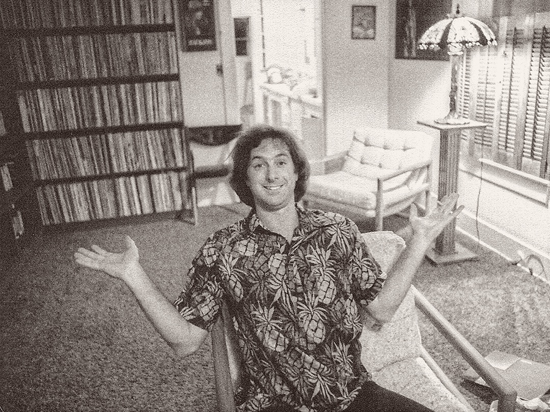 Ken Douglas in a black and white photo. He's wearing an Hawaiian shirt and his record collection is behind him.
