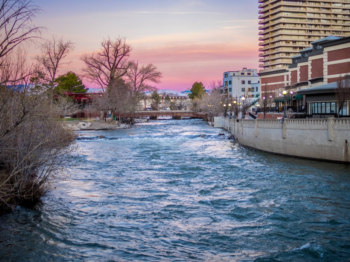 The Truckee River in Downtown Reno at Sunrise. The sky is pink.