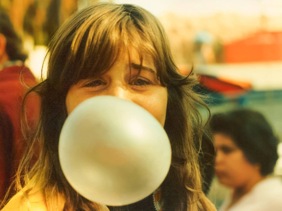 Bubble Gum Girl by Ken Douglas. This is a photograph of a young girl blowing a bubble gum bubble.