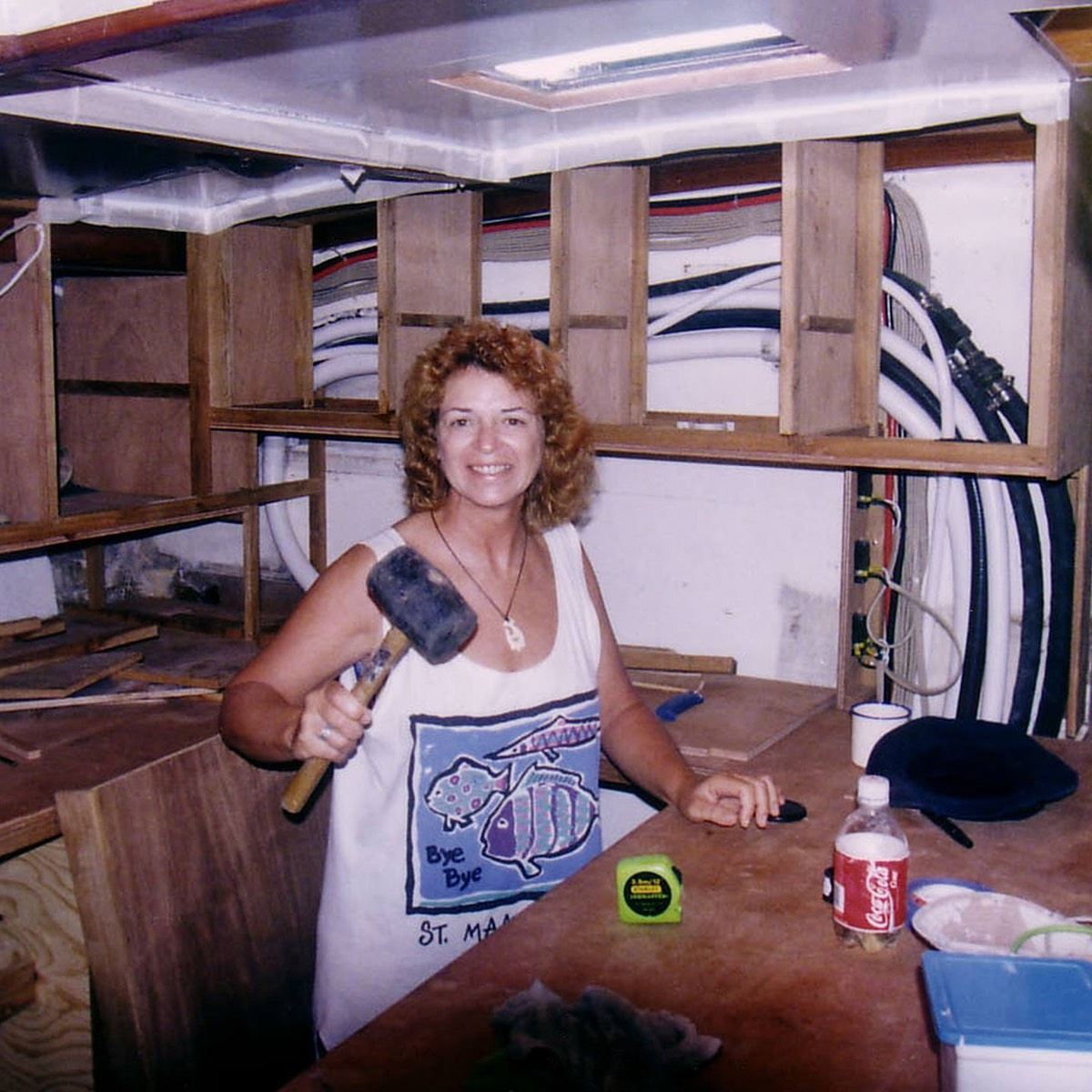 Vesta with a hammer working on building the galley in Great White Wonder, the sailboat we lived on in the Caribbean for ten years.