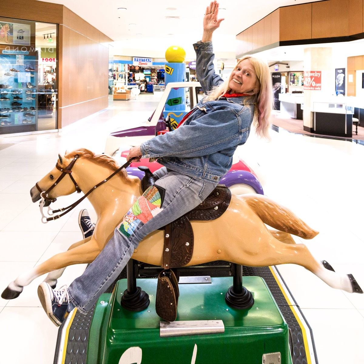 Vesta riding a dimestore horse in the mall.